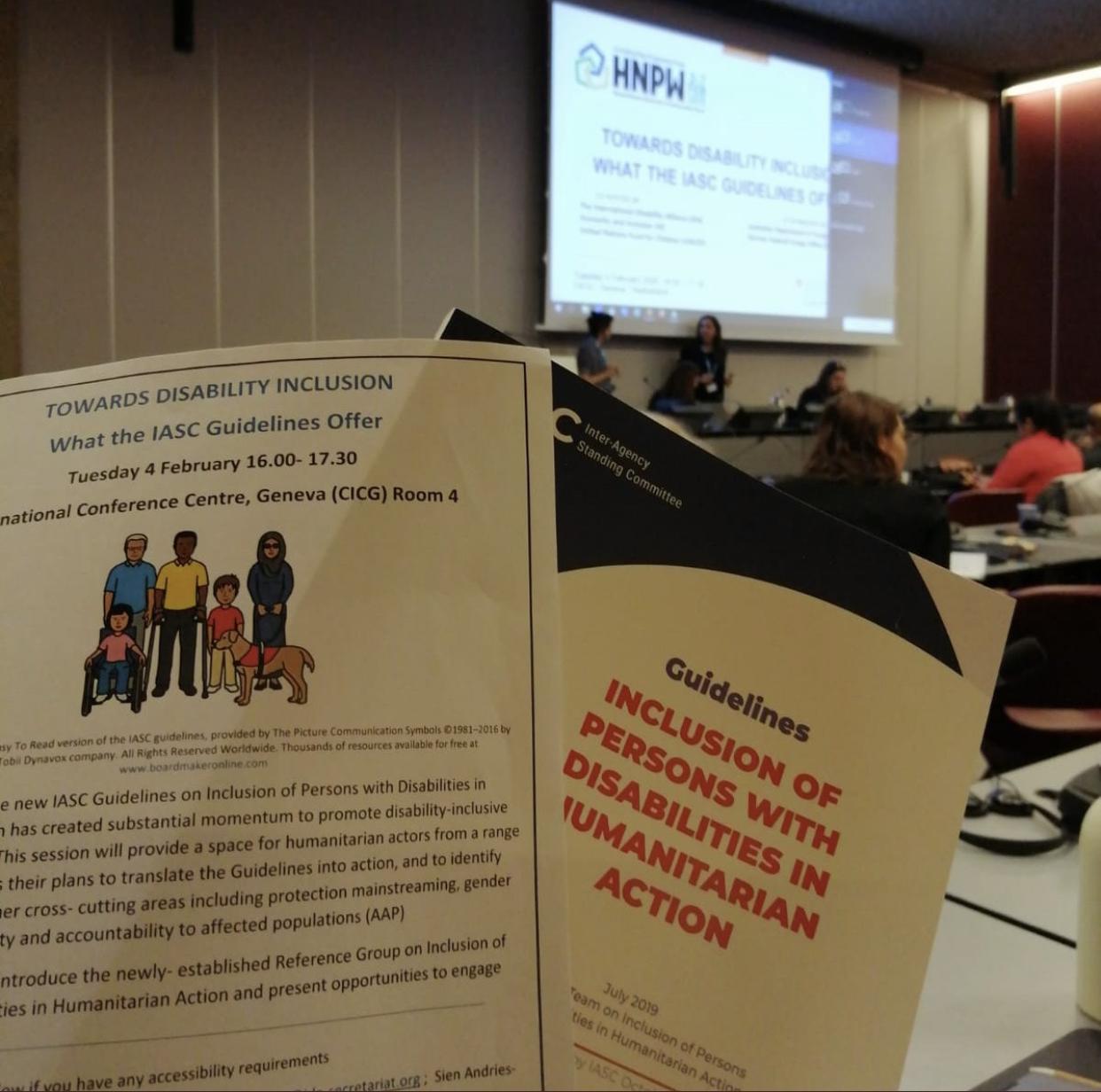 """Session auf der """"Humanitarian Network & Partnership Week"""" zur IASC-Leitlinien. Im Hintergrund stehen die Sprecher*innen. Im Vordergrund werden die Einladung und die IASC-Leitlinien hochgehalten."""